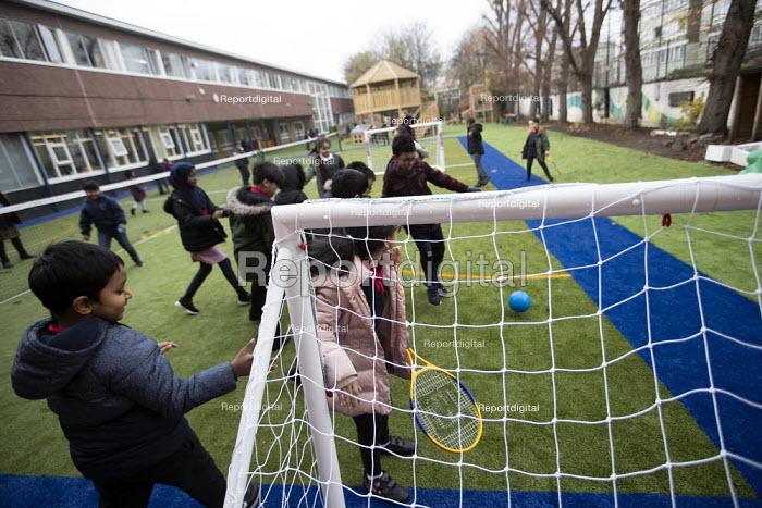 Playing football, breaktime, Lansbury Lawrence Primary School during Covid pandemic lockdown, Poplar, East London. - Jess Hurd - 2020-11-27