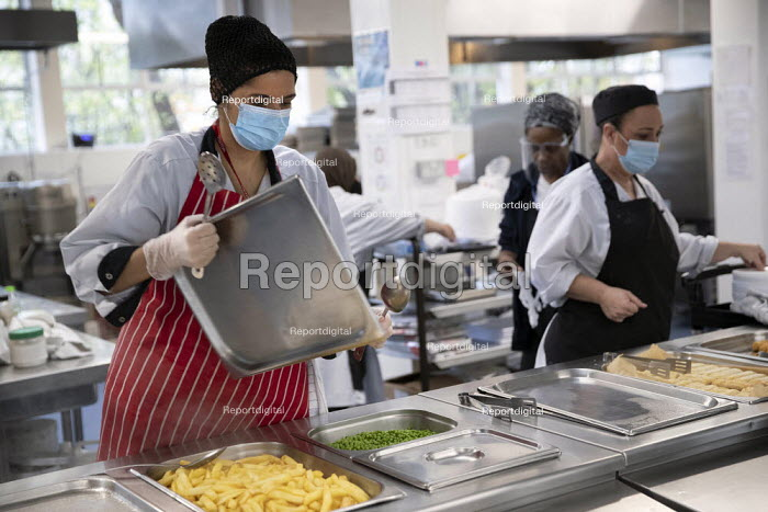 Kitchen staff wearing face masks and face visors. Lansbury Lawrence Primary School during Covid pandemic lockdown, Poplar, East London. - Jess Hurd - 2020-11-27