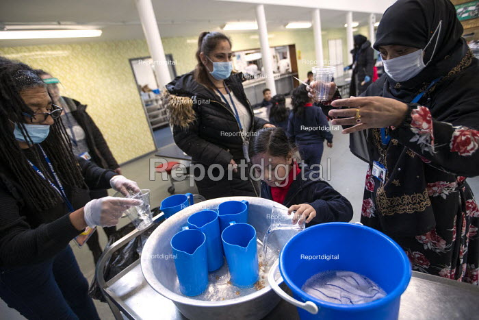 Staff wearing face masks and face visors. Dinner time, Lansbury Lawrence Primary School during Covid pandemic lockdown, Poplar, East London. - Jess Hurd - 2020-11-27