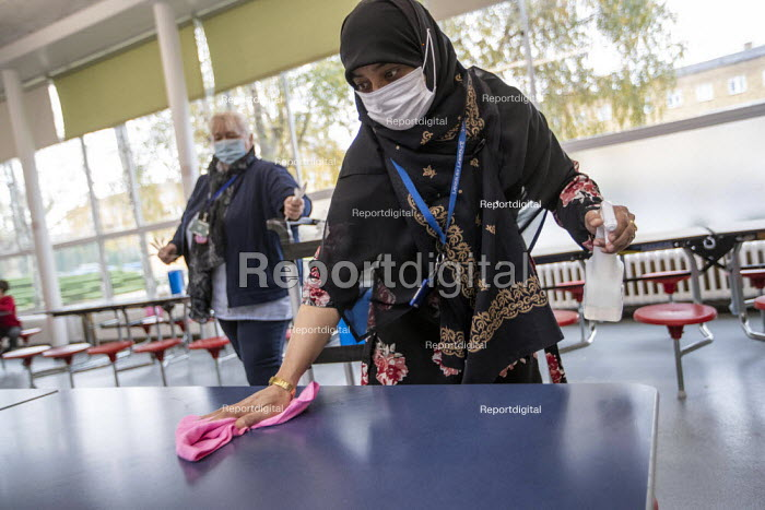 Dinner staff wearing face masks cleaning tables between each bubble. Lansbury Lawrence Primary School during Covid pandemic lockdown, Poplar, East London. - Jess Hurd - 2020-11-27