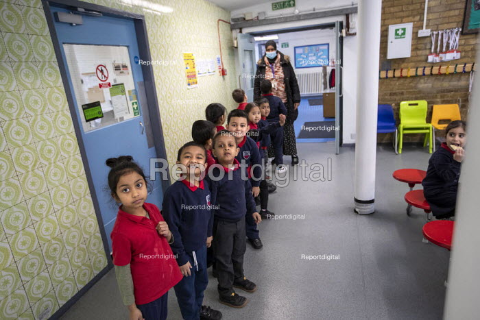 Staff wearing face masks. Bubble queuing at Dinner time, Lansbury Lawrence Primary School during Covid pandemic lockdown, Poplar, East London. - Jess Hurd - 2020-11-27