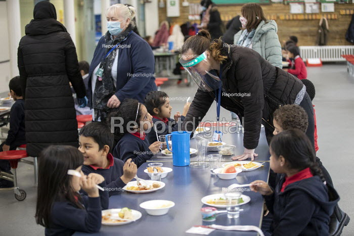 Staff wearing face visors. Dinner time, Lansbury Lawrence Primary School during Covid pandemic lockdown, Poplar, East London. - Jess Hurd - 2020-11-27