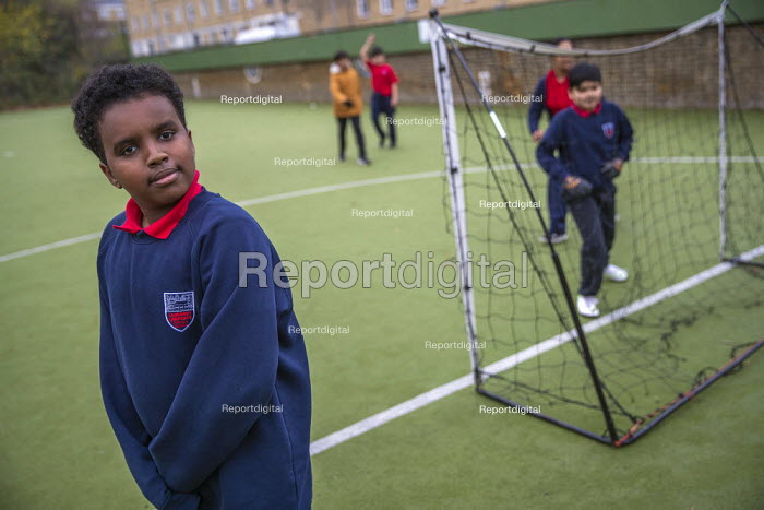 Playing football, Lansbury Lawrence Primary School during Covid pandemic lockdown, Poplar, East London. - Jess Hurd - 2020-11-27