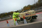 Road construction workers moving a compressor, M5 roadworks - John Harris - EBF, Economy, hire, LBR, maintenance, motorway, motorways, move, moving, push, pushing, road, roads, roadworks, tool, tools, Work, worker, workers,2010s,2015,Construction Industry,EBF,Economic,Economy