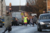 Lollipop lady stopping traffic so parents and children can cross the road as primary school pupils walking home after school, Goldthorpe - John Harris - 20-11-2015