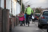 Primary school pupils walking home after school, Goldthorpe - John Harris - bicycles, child, children, cross, crossing, Crossing The Road, cycle, cycles, cycling, discuss, discussing, discussion, EDU, Education, father, fathers, girl, girls, man, men, pedestrians, Primary Sch