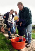 Reopening of Curbar and Froggatt Edges. Farther dunks his son in the disinfectant at Curbar Edge watched by his brother and a Peak Park Ranger. - David Bocking - 13-06-2001
