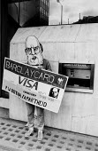 Anti Apartheid Movement protest Barclays Bank London 1985 with a Botha mask and Visa Barclaycard by a cash machine against the support given by Barclays Bank to the regime of P W Botha in South Africa - Paul Mattsson - 01-06-1985