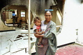 A mother and her child standing in their house, which was destroyed during the conflicts between the Pro Indonesian militia and the rebel forces, East Timor Crisis - Boris Heger - 2000s,2004,adult,adults,anti-independence,apparel,armed forces,Asia,asian,asians,babies,baby,BME minority ethnic,capital,carries,carry,carrying,child,CHILDHOOD,children,cities,city,clothes,clothing,co