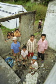 A family living in a temporary shelter, after their house was destroyed during the conflicts between the Pro-Indonesian militia and the rebel forces, in the East Timor Crisis. - Boris Heger - 2000s,2004,anti-independence,armed forces,Asia,asian,asians,BME minority ethnic,boy,boys,child,CHILDHOOD,children,communities,community,communties,conflict,conflicting,conflicts,crisis,Democratic,dest