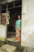 A woman standing in front of her house, which was destroyed during the conflicts between the Pro-Indonesian militia and the rebel forces, in the East Timor Crisis. - Boris Heger - 2000s,2004,anti social behavior,anti social behaviour,anti socialanti social behavior,anti-independence,antisocial,antisocial behaviour,antisocialvandalise,antisocialvandalize,armed forces,Asia,asian,