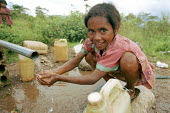 A child collecting water from a water point, which was recently rebuilt by a foreign NGO. After the previous one had been destroyed, during the conflicts between the Pro-Indonesian militia and the reb... - Boris Heger - (ICRC),(NGO),2000s,2004,agencies,agency,agricultural,agriculture,aid,aid agency,armed forces,Asia,asian,asians,assistance,BME minority ethnic,bottle,bottles,capital,charitable,charities,charity,child,