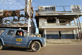 A taxi, passing houses, that were damaged during the conflicts between the Pro-Indonesian militia and the rebel forces, in the East Timor Crisis. - Boris Heger - 18-04-2004