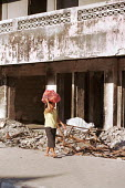 A woman carrying food on her head, while walking past houses that had been destroyed during the conflicts between the Pro-Indonesian militia and the rebel forces, in the East Timor Crisis. - Boris Heger - 2000s,2004,anti-independence,armed forces,Asia,asian,asians,BME minority ethnic,broken,building,buildings,capital,carries,carry,carrying,cities,city,conflict,conflicting,conflicts,crisis,Democratic,de