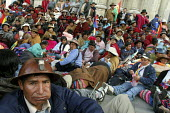 A miner chews coca leaves. Ponchos rojos (red coats), in background, an indigenous group supporting the President, protest outside parliament to put pressure on deputies from the opposition for them t... - Boris Heger - 20-10-2008