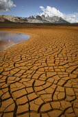 The cracked dried up mud of a reservoir which supplies water to the city of La Paz below the Huayna Potosi Mountain. The glaciers in the Andes are retreating, reducing the level to far lower than norm... - Boris Heger - 2000s,2009,americas,Andes,Bolivia,Bolivian,Bolivians,capped,Climate Change,country,countryside,degradation,Dried Up,drought,dry,eni,environment,Environmental,Environmental Issues,glacier,glaciers,Glob