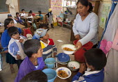 Children receiving a free meal at their school, as part of a state and NGO sponsored food program in Bolivia. - Boris Heger - 08-03-2010