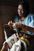 Women making traditional Tule handicrafts, spinning cloth. This village of Indigenous Tule have been displaced by conflict, to the Panama border region of the Darien gap. There are only a few thousand... - Boris Heger - 2010,2010s,ACE,americas,Amerindian,Amerindians,apparel,applique,art,artisan,artisans,border,by hand,communities,community,conflict,costume,costumes,craft,crafts,craftsman,culture,Cuna,darien,Darien Ga
