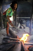 A Tule woman cooking in her home. This village of Indigenous Tule have been displaced by conflict, to the Panama border region of the Darien gap. There are only a few thousands Tule left and their lan... - Boris Heger - 2010,2010s,americas,Amerindian,Amerindians,border,communities,community,conflict,cook,COOKERY,cooking,cooks,costume,costumes,Cuna,darien,Darien Gap,displaced,displacement,domestic,Dule,dulemola,employ