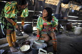 Tule women cooking in their home. This village of Indigenous Tule have been displaced by conflict, to the Panama border region of the Darien gap. There are only a few thousands Tule left and their lan... - Boris Heger - 2010,2010s,ACE,americas,Amerindian,Amerindians,border,communicating,communication,communities,community,conflict,conversation,conversations,cook,COOKERY,cooking,cooks,costume,costumes,Culture,Cuna,dar