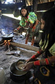 Tule women cooking in their home. This village of Indigenous Tule have been displaced by conflict, to the Panama border region of the Darien gap. There are only a few thousands Tule left and their lan... - Boris Heger - 2010,2010s,americas,Amerindian,Amerindians,border,communicating,communication,communities,community,conflict,conversation,conversations,cook,COOKERY,cooking,cooks,costume,costumes,Cuna,darien,Darien G