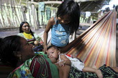 A woman breastfeeding her child. This village of Indigenous Tule have been displaced by conflict, to the Panama border region of the Darien gap. There are only a few thousands Tule left and their lang... - Boris Heger - 2010,2010s,adult,adults,americas,Amerindian,Amerindians,babies,baby,border,boy,boys,breastfeeding,CARE,carer,carers,child,Child Care,Child Carer,Child Carers,childcare,CHILDHOOD,CHILDMINDING,children,