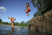 Children playing, jumping into the river. This village of Indigenous Tule have been displaced by conflict, to the Panama border region of the Darien gap. There are only a few thousands Tule left and t... - Boris Heger - 04-05-2010