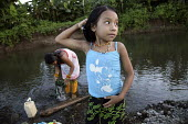 A girl washing in a local river. This village of Indigenous Tule have been displaced by conflict, to the Panama border region of the Darien gap. Their culture is based on a strong relationship with th... - Boris Heger - 2010,2010s,americas,Amerindian,Amerindians,border,child,CHILDHOOD,children,clean,cleaning,cleansing,communities,community,conflict,Cuna,darien,Darien Gap,displaced,displacement,Dule,female,females,gir