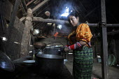 A Tule woman cooking in her hut. This village of Indigenous Tule have been displaced by conflict, to the Panama border region of the Darien gap. Their culture is based on a strong relationship with th... - Boris Heger - 2010,2010s,americas,Amerindian,Amerindians,border,communities,community,conflict,cook,COOKERY,cooking,cooks,costume,Cuna,darien,Darien Gap,displaced,displacement,domestic,Dule,dulemola,FEMALE,house,ho