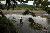A man crossing a local river. This village of Indigenous Tule have been displaced by conflict, to the Panama border region of the Darien gap. Their culture is based on a strong relationship with the l... - Boris Heger - 05-05-2010