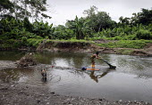 A Tule woman washing clothes in a local river. This village of Indigenous Tule have been displaced by conflict, to the Panama border region of the Darien gap. Their culture is based on a strong relati... - Boris Heger - 2010,2010s,access,americas,Amerindian,Amerindians,animal,animals,apparel,border,clean,cleaning,cleansing,clothes,clothing,communities,community,conflict,country,countryside,Cuna,darien,Darien Gap,Depa