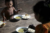 A Tule family eating a meal in their hut. This village of Indigenous Tule have been displaced by conflict, to the Panama border region of the Darien gap. There are only a few thousands Tule left and t... - Boris Heger - 2010,2010s,americas,Amerindian,Amerindians,border,boy,boys,child,CHILDHOOD,children,communities,community,conflict,Cuna,darien,Darien Gap,Darien National Park,displaced,displacement,Dule,eat,eating,fa