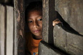 A Tule boy looking out of his hut. This village of Indigenous Tule have been displaced by conflict, to the Panama border region of the Darien gap. There are only a few thousands Tule left and their la... - Boris Heger - 2010,2010s,americas,Amerindian,Amerindians,border,boy,boys,child,CHILDHOOD,children,communities,community,conflict,Cuna,darien,Darien Gap,Darien National Park,displaced,displacement,door,doors,Dule,ho