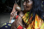 A grandmother singing a traditional song to her grandchild in the native language, Dulegaya, and with a rattle.. Most younger Tule do not know the meaning of that song anymore, as the traditional dial... - Boris Heger - 05-05-2010