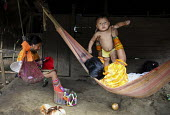 A Tule family relaxing in hammocks. They rest with a siesta during the hottest part of the day. This village of Indigenous Tule have been displaced by conflict, to the Panama border region of the Dari... - Boris Heger - 2010,2010s,ACE,adult,adults,americas,Amerindian,Amerindians,arts,border,boy,boys,CARE,carer,carers,child,Child Care,Child Carer,Child Carers,childcare,CHILDHOOD,CHILDMINDING,children,communities,commu