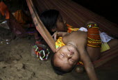 A baby asleep in a hammock. The Tule rest with a siesta during the hottest part of the day. This village of Indigenous Tule have been displaced by conflict, to the Panama border region of the Darien g... - Boris Heger - 05-05-2010
