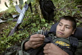A FARC guerilla looking at his bullets while resting under cover, after a long night walking in the forest. - Boris Heger - 24-06-2010
