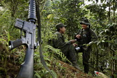 Two women members of the FARC guerilla chat and laugh under cover to evade helicopter searches, after a long night walking in the forest - Boris Heger - 2010,2010s,americas,Amerindian,Amerindians,armed,Armed Forces,arms,army,camp,camps,Civil War,Colombia,Colombian,Colombians,columbian,columbians,communicating,communication,communism,Communist Party,co