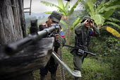 Two members of the FARC guerilla observe an army position prior to their attack - Boris Heger - 24-06-2010