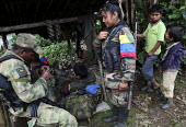 Members of the FARC guerilla clean and maintain their weapons during a rest. A couple of boys from a local village watch - Boris Heger - 25-06-2010