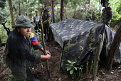 Members of the FARC guerilla hidden under trees pack their bags and tents as soon as they wake up in readiness. - Boris Heger - 26-06-2010