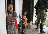 Children watch from their house as members of the FARC guerilla pass through their village. - Boris Heger - ,2010,2010s,47,AK,AK 47,AK47,AK47S,americas,Amerindian,Amerindians,animal,animals,armed,Armed Forces,arms,army,boy,boys,canine,child,CHILDHOOD,children,Civil War,Colombia,Colombian,Colombians,columbia