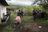 Young indigenous child rides his bicycle in front of his house as members of the FARC guerrillas stand around during a break from the fighting - Boris Heger - ,2010,2010s,americas,Amerindian,Amerindians,armed,Armed Forces,arms,army,bicycle,bicycles,BICYCLING,Bicyclist,Bicyclists,BIKE,BIKES,boy,boys,break,bycicle,child,CHILDHOOD,children,Civil War,Colombia,C