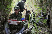 A member of the FARC guerilla reads a book by Lenin during a rest, Colombia - Boris Heger - ,2010,2010s,americas,Amerindian,Amerindians,armed,Armed Forces,arms,army,belt,book,books,Bullet,bullets,camp,camps,Civil War,Colombia,Colombian,Colombians,columbian,columbians,communism,Communist Part