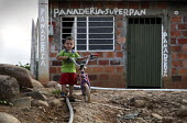 An idp boy playing with his bike by a bakery in a poor area of Cucuta. The deteriorating security situation in the regions on the border with Venezuela has led to more than 15000 seeking refuge in the... - Boris Heger - 26-05-2010