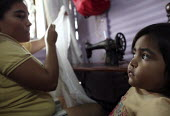 A young colombian refugee watches on as her mother works at home to try to sustain her family. The deteriorating security situation in the regions on the border with Venezuela has led to more than 150... - Boris Heger - 2010,2010s,adult,adults,americans,americas,Amerindian,Amerindians,apparel,Barrio,Barrios,border,child,childhood,children,cities,city,clothing,Colombia,Colombian,columbian,columbians,Diaspora,displaced