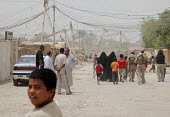 Internal displaced people (IDPs) walk past American troops at a makeshift camp near Chikook suburb of north-west Baghdad, Iraq, July 23, 2009. - Boris Heger - , Iraqis,2000s,2009,american,americans,Arab,Arabs,armed forces,army,camp,camps,Diaspora,displaced,displacement,foreign,foreigner,foreigners,IDP,IDPs,immigrant,IMMIGRANTS,immigration,internally,Interna