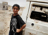 An internal displaced boy(IDPs) stand by a destroyed vehicle at a makeshift camp near Chikook suburb of north-west Baghdad, Iraq, July 23, 2009. - Boris Heger - , Iraqis,2000s,2009,adolescence,adolescent,adolescents,Arab,Arabs,boy,boys,camp,camps,child,CHILDHOOD,children,destroyed,DESTRUCTION,Diaspora,displaced,displacement,foreign,foreigner,foreigners,idp,ID