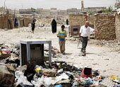 Internal displaced people (IDPs) dump rubbish in the open at a makeshift camp near Chikook suburb of north-west Baghdad, Iraq, July 23, 2009. - Boris Heger - , Iraqis,2000s,2009,Arab,Arabs,Asylum Seeker,Asylum Seeker,boy boys,camp,camps,CHILD,child children,CHILDHOOD,children,Diaspora,displaced,displacement,dump,families,family,FEMALE,foreign,foreigner,for
