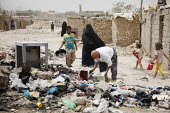 Internal displaced people (IDPs) throw away rubbish in the street at a makeshift camp near Chikook suburb of north-west Baghdad, Iraq, July 23, 2009. - Boris Heger - , Iraqis,2000s,2009,Arab,Arabs,Asylum Seeker,Asylum Seeker,boy boys,camp,camps,CHILD,child children,CHILDHOOD,children,Diaspora,displaced,displacement,dump,families,family,FEMALE,foreign,foreigner,for